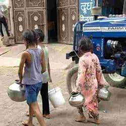 आगरा के ताजगंज इलाके में तुलसी चबूतरा के पास पानी के लिए बर्तन लेकर जाती बच्चियां।