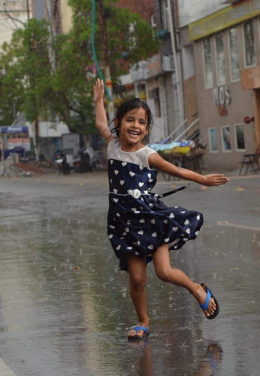 आगरा की बारिश में आनंद लेते हुए एक मासूम बच्ची।