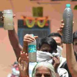 आगरा के शहीद नगर में प्रदर्शन करते हुए गंदे पानी को दिखाती एक बूढ़ी महिला।
