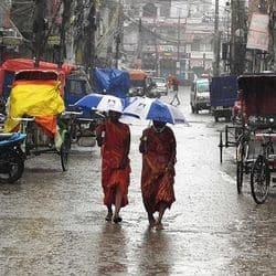 बारिश में छाता से खुद को बचाती दो महिलाएं।
