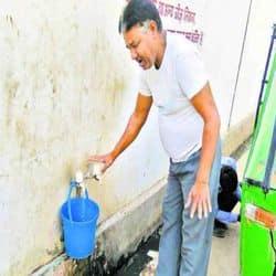 नल से पानी लेता एक व्यक्ति।