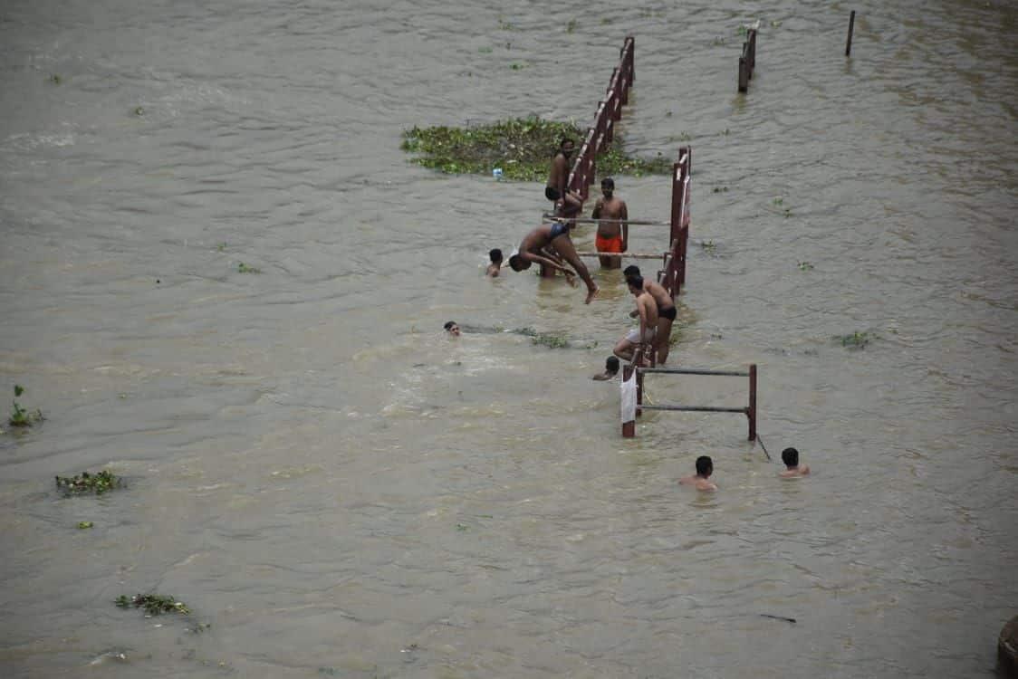 तुलसी घाट पर बढ़ते जलस्तर में जान जुखिम में डालकर लोग कर रहे मस्ती