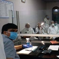 दिल्ली -मेरठ एक्सप्रेसवे निर्माण कार्य से जुड़े विवाद पर बैठक करते किसान और एनएचआई के अधिकारी