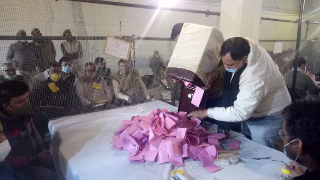 एमएलसी चुनाव में मतगणना स्थल पर गणना की प्रकिया शुरु करते कर्मचारी