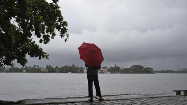 A man stands by the sea as it drizzles in Kochi in Kerala on May 28, 2018. (AP)