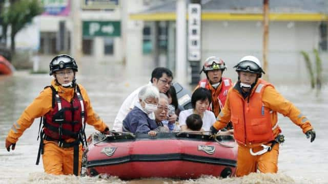 Local residents sit in a boat as they are rescued from a flooded area at a hospital in Kurashiki, Ok