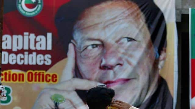 A Pakistani talks on his cell phone while he sits on a bench next to a big poster of Imran Khan(AP)