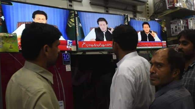 Pakistani men gather around a bank of televisions in a store as they watch a broadcast of a speech o