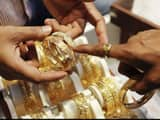 An employee shows gold bangles to a customer at a jewellery showroom on Dhanteras in Mumbai. (Reuter
