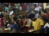 Flood affected people eat a meal as they crowd a relief camp set up inside a school in Kochi, Kerala
