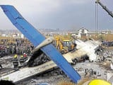 Rescue workers work at the wreckage of a US-Bangla airplane after it crashed at the Tribhuvan Intern