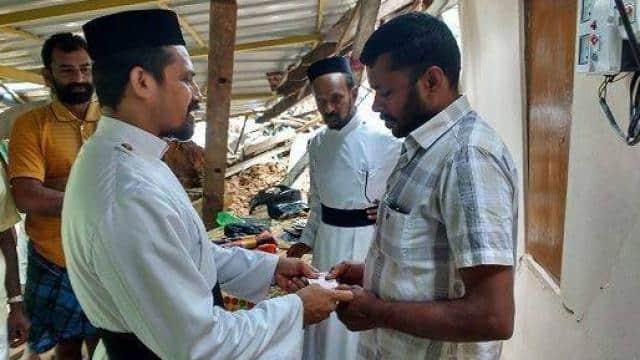 बाढ़ प्रभावित लोगों को आर्थिक मदद देते फादर सीजू जॉर्ज