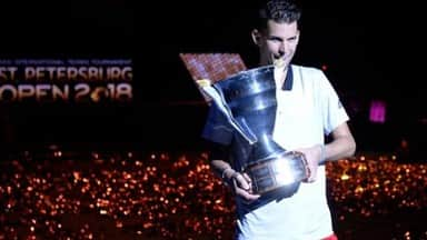 Austrian Dominic Thiem poses with his victory trophy after defeating Slovakia Martin Klizan