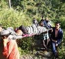 घायल महिला को चारपाई पर रखकर सड़क तक लाए ग्रामीण