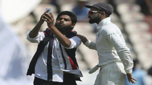 A cricket fan enters the pitch to take a selfie and hug Virat Kohli (Photo by NOAH SEELAM / AFP)