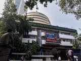 People watch share prices on a digital broadcast outside the Bombay Stock Exchange (BSE) in Mumbai o