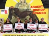 Nuns hold placards during a protest demanding justice after an alleged sexual assault of a nun by a