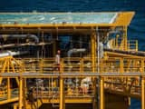 A worker passes a helicopter landing pad aboard an offshore oil platform in the Persian Gulf's Salma