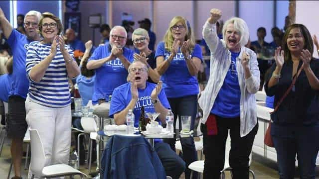 Democratic supporters react as the networks begin calling house races for Democrat candidates as the
