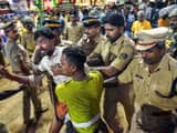 Police personnel detain the devotees who were staging 'Namajapa' protest against the police restrict