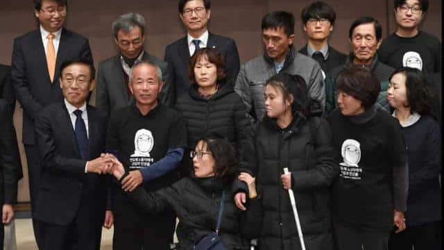 Samsung Electronics co-president Kim Ki-nam (L) poses for a photo with relatives of victims of work-