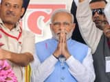 Prime Minister Narendra Modi being garlanded during a public meeting for Madhya Pradesh Assembly ele