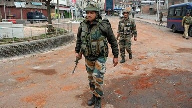 Army personnel patrol the street during a curfew in Jammu on fourth day