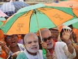 bjp supporters wear saree imprinted with pm narendra modi portrait and hold party flags in election