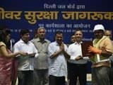 delhi cm arvind kejriwal felicitates a worker during a safety awareness workshop