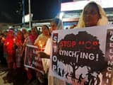 women hold placards and candles during a protest against the recent mob lynchings across the country