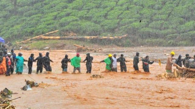 rescuers help people to cross a flooded area after a landslide caused by torrential monsoon rains in