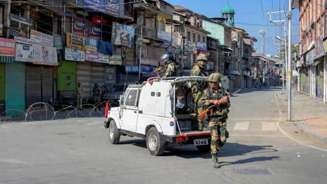 security personnel stands guard at a road in srinagar on monday  september 9  2019   pti