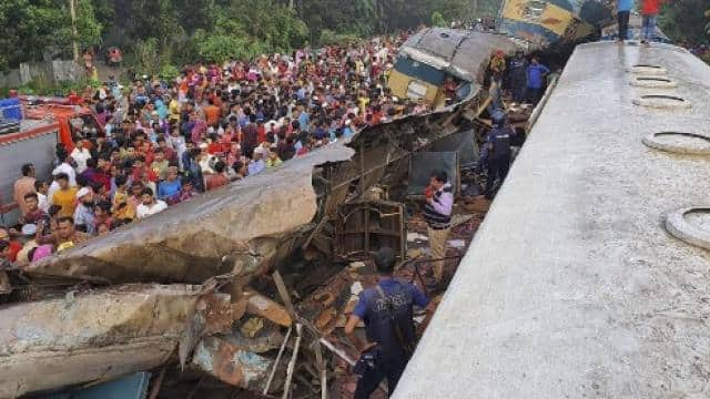 people gather near badly damages coaches after two speeding trains collided in dhaka