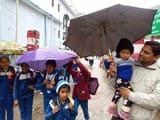 भारी बारिश में भीगते हुए स्कूल से लौटे बच्चे