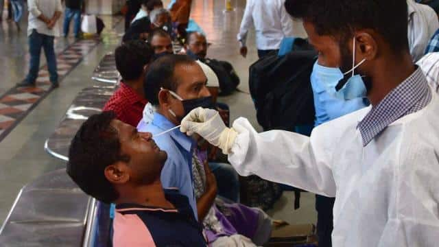 A health worker in PPE coveralls collects a swab sample from a passenger for Covid-19 test (HT Photo)